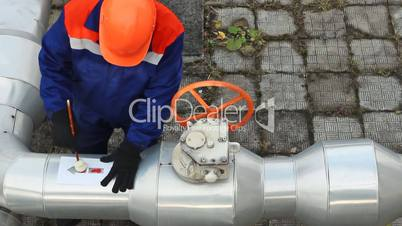 Worker draws red arrow on pipes