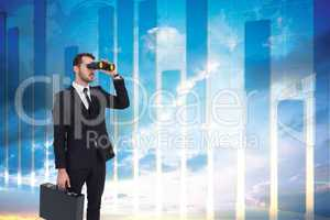 Composite image of businessman holding a briefcase while using b