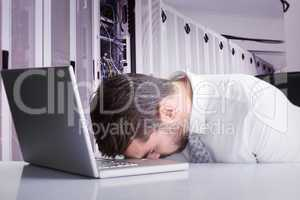 Composite image of exhausted businessman sleeping head on laptop