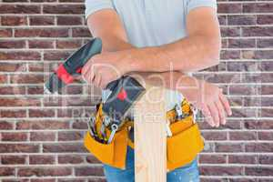 Composite image of midsection of male carpenter with power drill