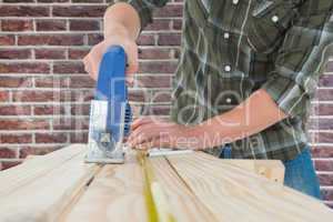 Composite image of carpenter cutting wooden plank with electric