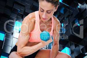 Composite image of strong woman doing bicep curl with blue dumbb
