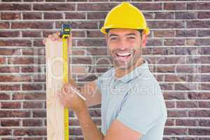 Composite image of construction worker using measure tape to mar
