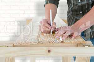 Composite image of carpenter marking on wooden plank