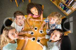 College students holding coffee mugs on table