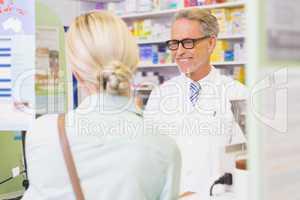 Senior pharmacist speaking with customer