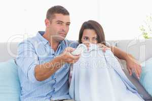Couple watching horror movie on sofa