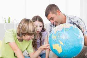 Children exploring globe while sitting with father