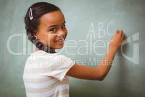 Cute little girl writing ABC on blackboard