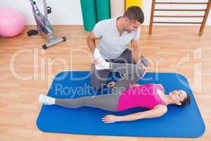 Trainer working with woman on exercise mat