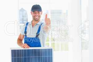 Workman with solar panel gesturing thumbs up in bright office