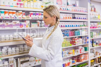 Pharmacy intern writing on clipboard
