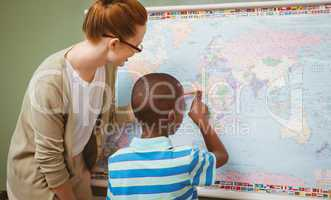 Teacher assisting boy to read map in classroom