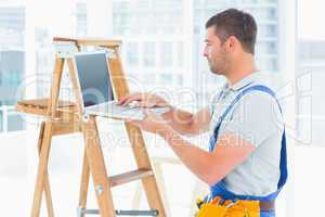Handyman using laptop by ladder in bright office