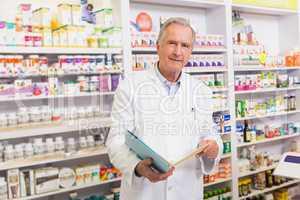 Smiling senior pharmacist holding notebooks