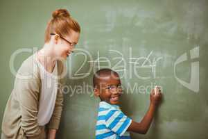 Teacher assisting boy to write on blackboard in classroom