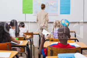 Naughty pupil about to throw paper airplane in class
