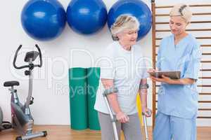 Therapist and senior woman looking at clipboard