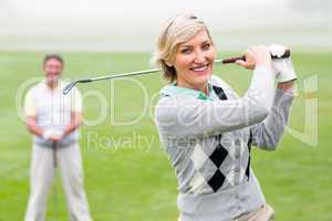 Lady golfer teeing off for the day watched by partner