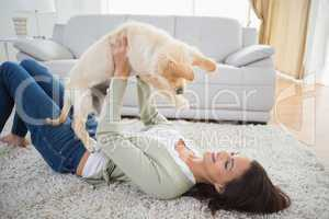 Woman lifting puppy while lying on rug