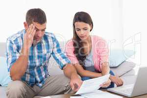 Couple reading bill while calculating home finances