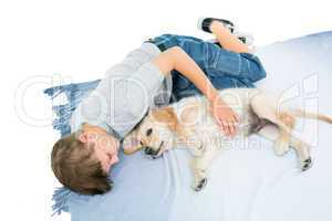 Boy lying with puppy on blanket over white background