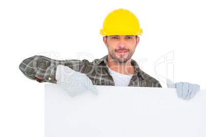 Handyman holding and pointing at blank board