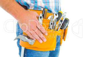 Midsection of handyman wearing tool belt