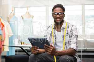 Confident male fashion designer with digital tablet