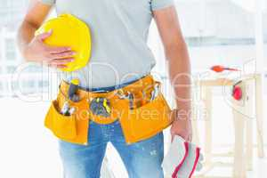 Handyman with gloves and helmet at construction site