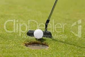 Golf club putting ball at the hole