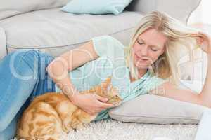 Woman stroking cat while playing with hair on rug