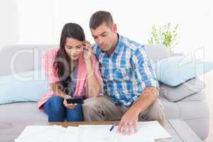 Couple calculating home finances at table
