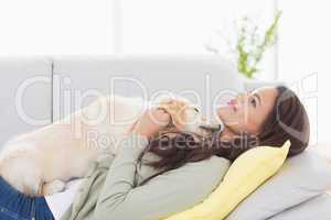 Woman with puppy lying on sofa