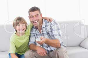 Happy father and son using remote control on sofa