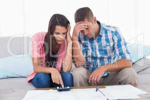 Tensed couple calculating home finances