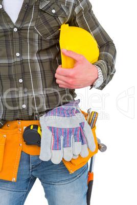 Manual worker wearing tool belt while holding helmet