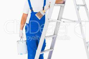 Handyman with paintbrush and can on ladder