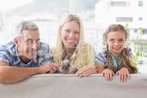 Happy family with rabbit on sofa at home
