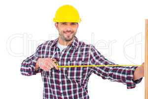Handyman using measure tape on wooden plank