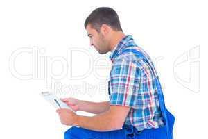 Handyman reading clipboard on white background