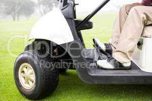 Golfer driving his golf buggy