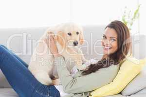 Woman playing with puppy on sofa at home