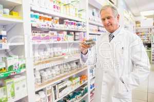 Smiling senior pharmacist holding blister