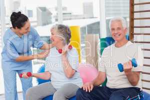 Trainer communicating with senior woman sitting by man
