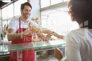 Smiling baker doing loaf transaction with customer