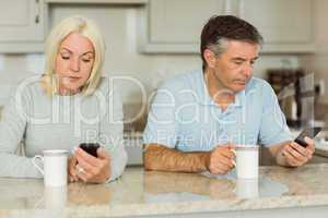 Mature couple having coffee and using phones