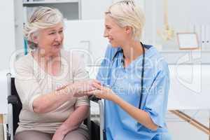 Female nurse checking flexibility of patients wrist