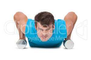 Fit man doing push ups with dumbbells