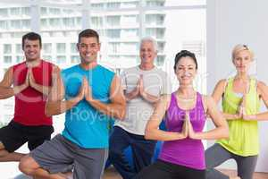 People practicing tree pose in fitness studio